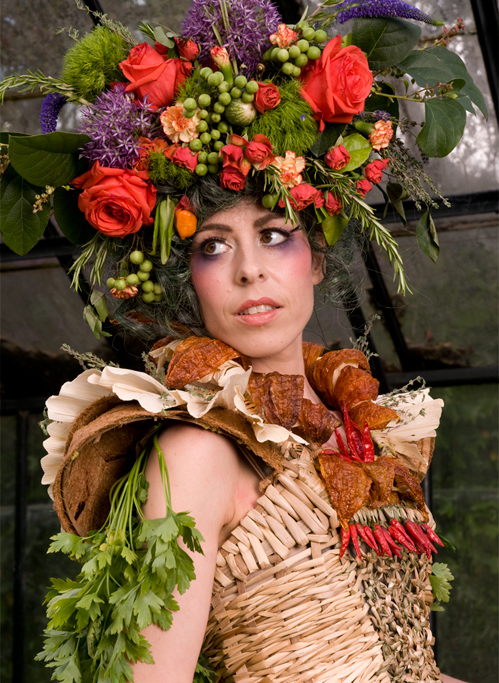 Madame Jardin wears an elaborate headpiece of edible flowers. Her bustier is woven with Tule, Cattail and basketry reed. The collar is made from Peruvian Chilies, Corn Husks and Coconut Pots with a dash of Cilantro.