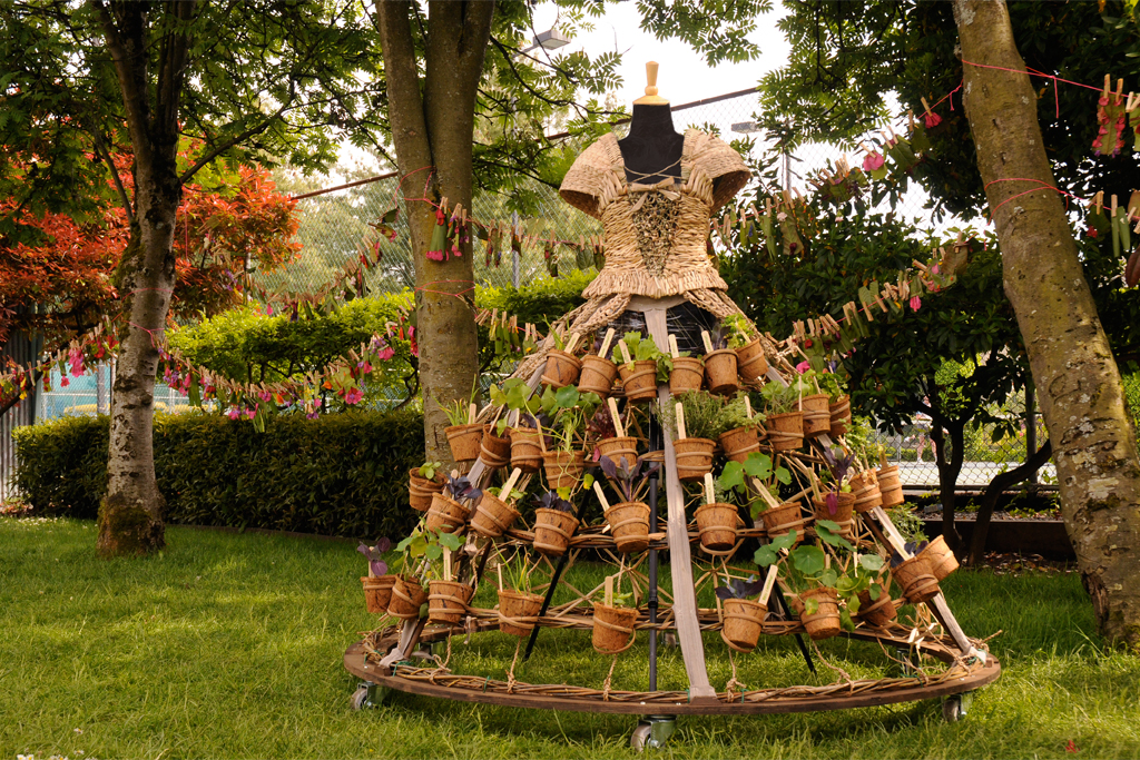 The Mobile Garden Dress installed at the Children's Festival. In the background hangs the Eco-Fashion Clothesline made by local children attending the festival.