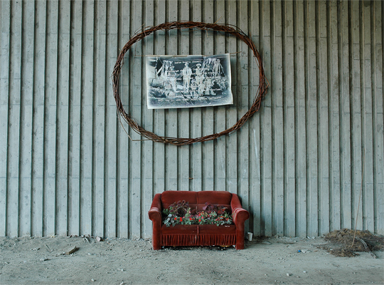 Snauq Garden - A photo of the original native inhabitants of the area once called Snauq framed by a crown of thorns is placed above a red sofa acting as a flower bed for shade plants.