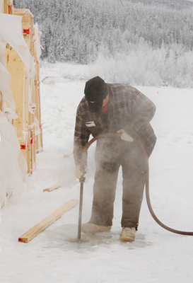 Steam Drilling the Yukon - Worker uses a steam head to melt a hole in the 4 feet deep river ice, from which water will be pumped into the wooden form and left to freeze for several weeks.