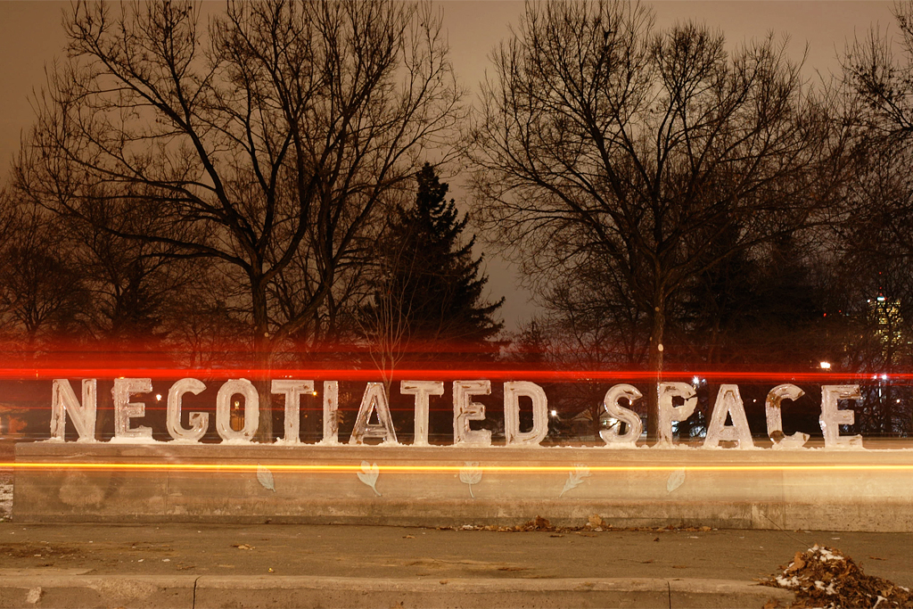 Negotiated Space - Installed at the edge of Trinity Bellwoods park. Shot at night with cars driving past.