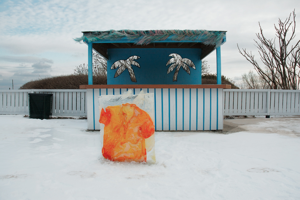Tropical Beach Stand - Man's short sleeved sunny orange shirt in contrast to the abandoned amusement park stand on a blustery winter day.