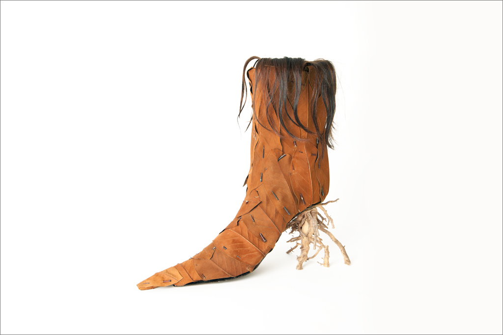 The Magnolia Pubescence Ankle Boot combines the fetish for elongated toes with the absurdity of balancing one's heel on a delicate root. Made from dried Magnolia leaves, root, Cattail, leather, thorns and the artists' hair.
