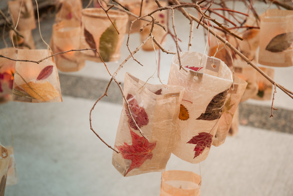 Lanterns hanging from the chandelier branches. Made from wax paper, pressed leaves and cardboard.