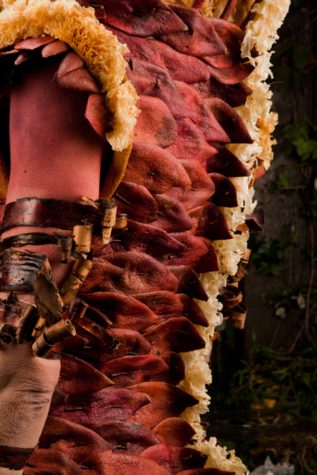Back detail of pomegranate jacket with a spine design made from dried mushrooms held together with thorns. Armbands made from bark.